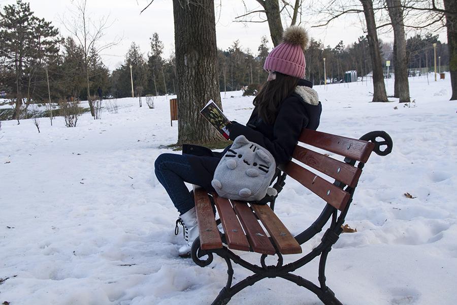 fata citind pe banca in parc iarna